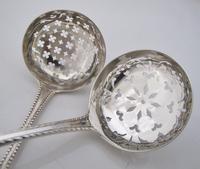 Two similar Georgian Crested Silver Sifter Spoons John Lamb London 1771