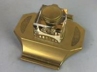 Art Deco brass and glass inkwell, the hinged brass lid above a clear glass body and brass base with two pen trays and engraved foliate scroll decoration, (10 of 12)
