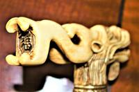 A finely carved large and chunky Chinese bone walking stick depicting a dragon with a loose ball in its mouth (5 of 6)